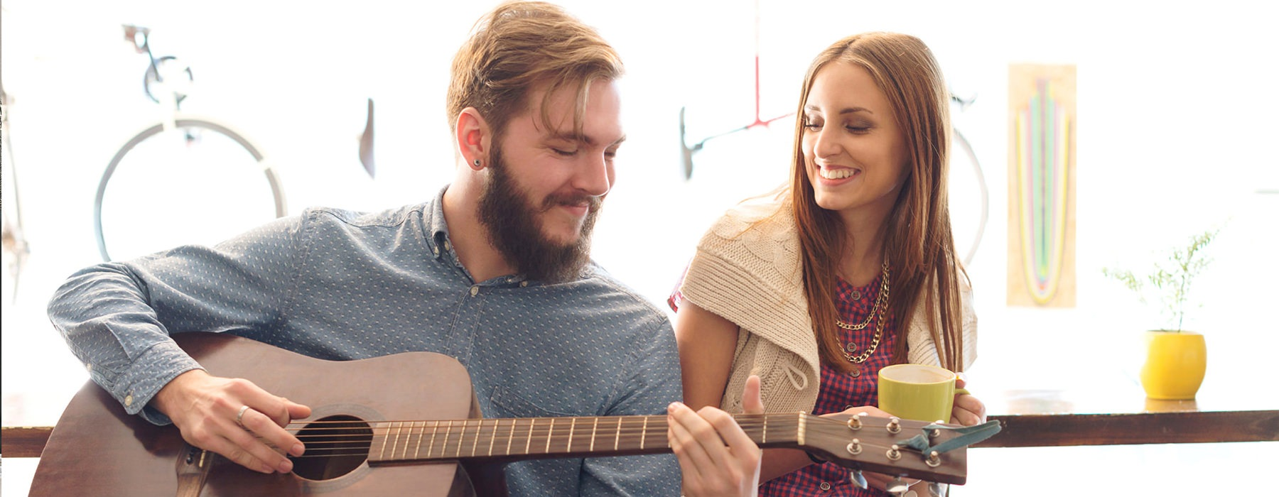 Couple hanging out while the man plays guitar